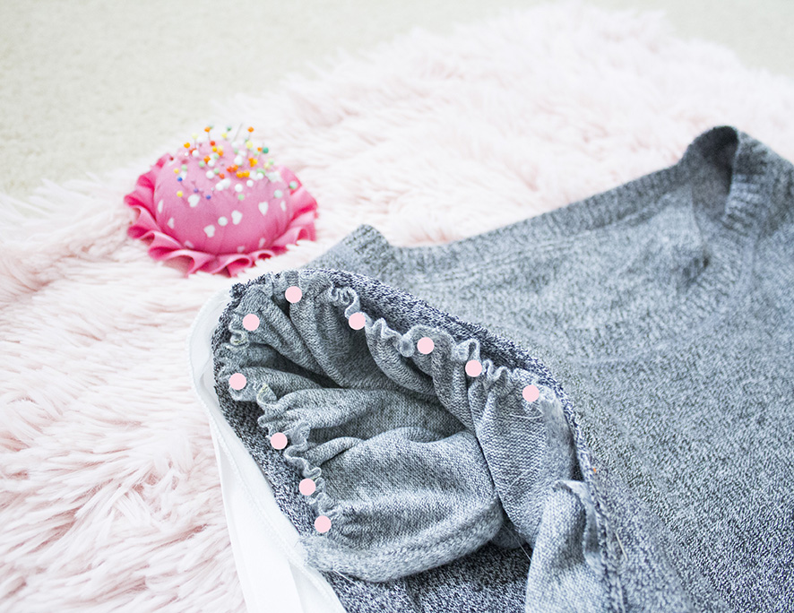 close up of grey sweater with ruffle piece pinned to it
