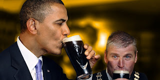 President Barack Obama in a dark suit and white shirt drinking a glass of dark Guinness beer. There is another grey-haired man also drinking in the background.