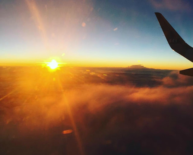 A photo showing the sun just above the clouds taken from an aircraft window.  The edge of the wing is visible on the right and the clouds are glowing shades of gold and red. It could be sunrise or sunset.