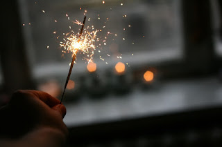 Image of someone holding a lit sparkler