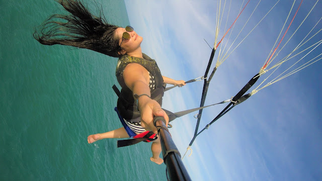 mulher voando de parasail