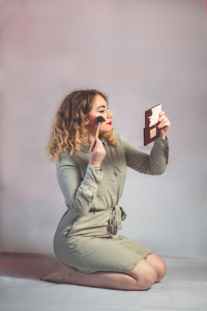 woman kneeling and applying makeup while looking in hand held mirror: