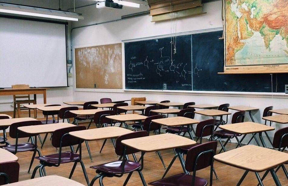 A imagem mostra uma sala de aula vazia com mesas, cadeiras e lousa