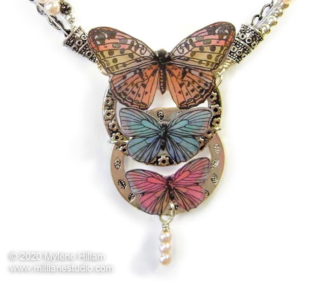 Butterfly and pearl necklace with 3 pastel butterflies attached in descending sizes to 2 vertically connected metal rings.