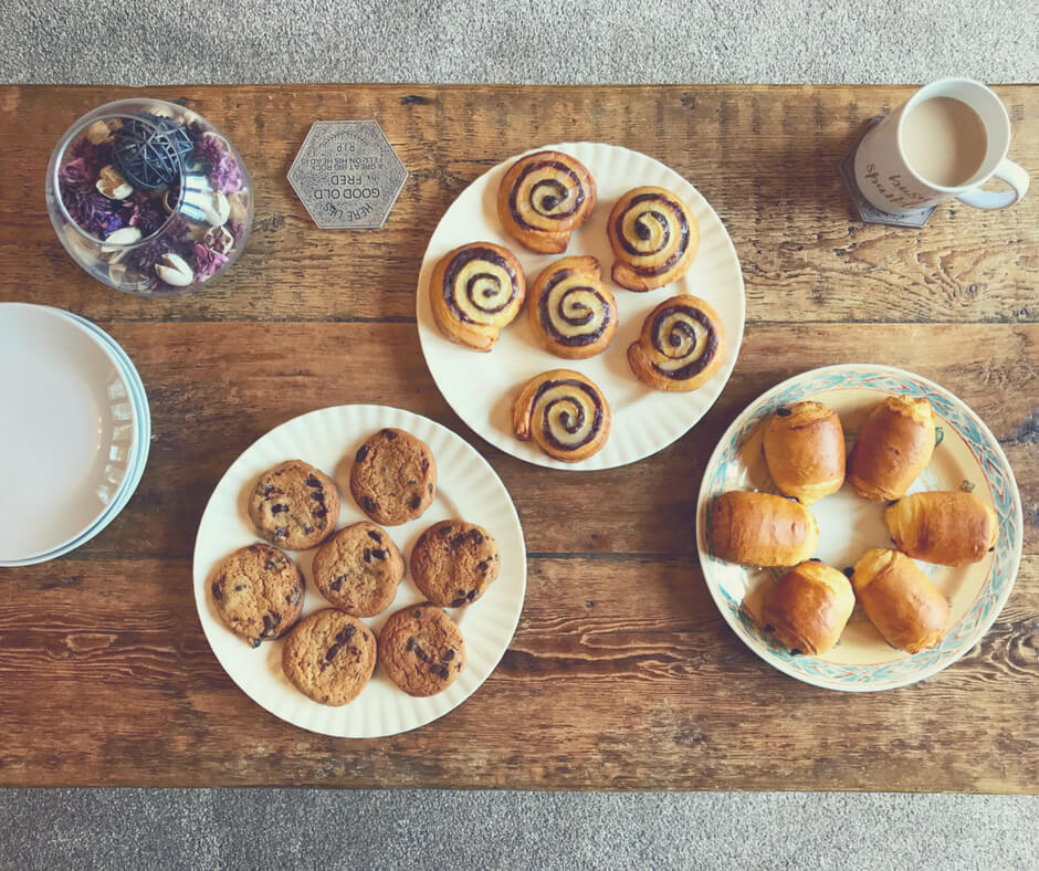 Cinnamon rolls and pain au chocolate laid out on a wooden table. Breakfast for the family.