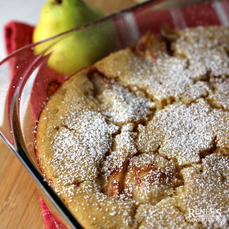 Overhead view of finished Warm Pear Cobbler by Renee's Kitchen Adventures in pan with one fresh pear in the background