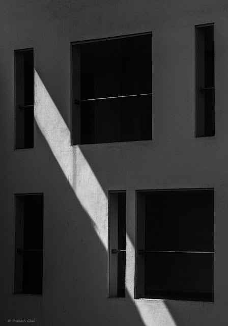 A Black and White Minimalist Photograph of a Streak of Light on the Facade of a Building with multiple Windows.