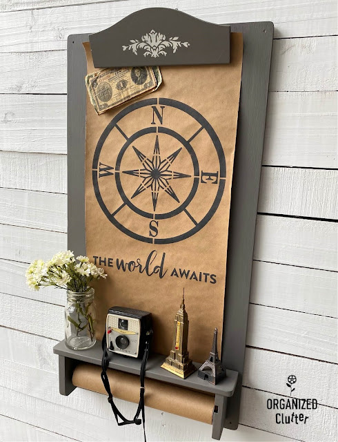 Photo of a child's wall art easel repurposed as wall decor with paint and stencils and staged with accessories.
