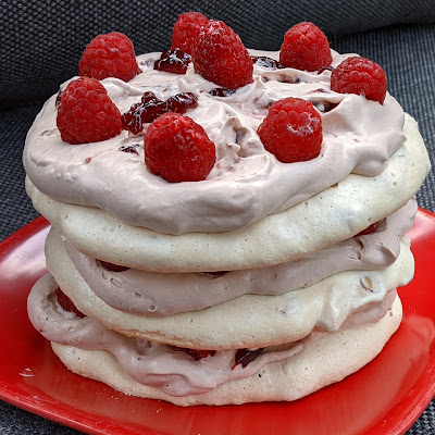 three discs of creamy white dacquoise on a red plate, alternating with layers of rosy brown ovaltine whipped cream, raspberry jam, and fresh raspberries