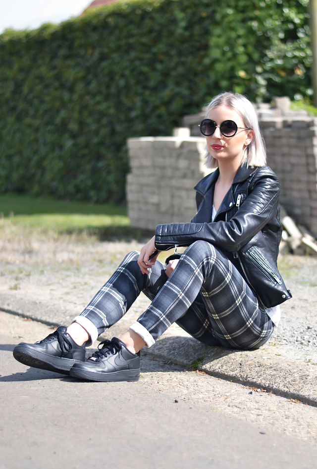 Outfit post of Belgian fashion blogger: Zara leather jacket, h&m divided, v neck, oversized white t-shirt, mango tartan trousers, nike aire force 1 sneakers black, mango leather backpack, primark round sunglasses. Street style inspiration 2015