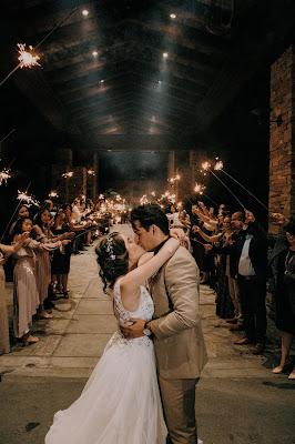 Novios besándose en el pasillo nupcial formado por los invitados que agitan bengalas