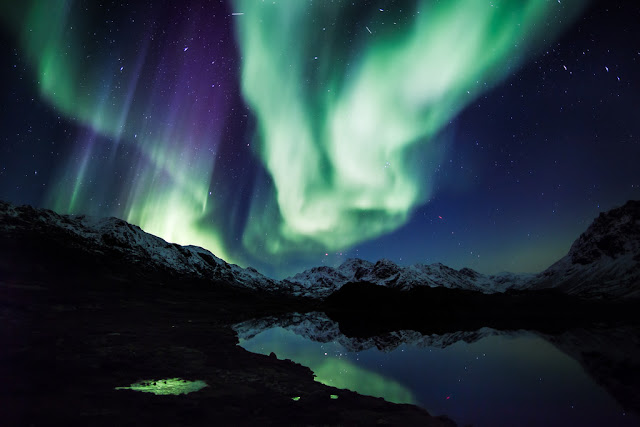 green northern lights over mountains and lakes