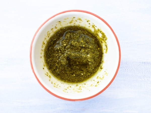 small white bowl half filled with pesto