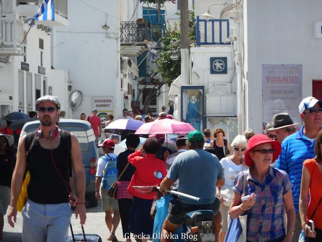 ludzie w letnich ubraniach idą po ulicy greckiej wyspy Mykonos