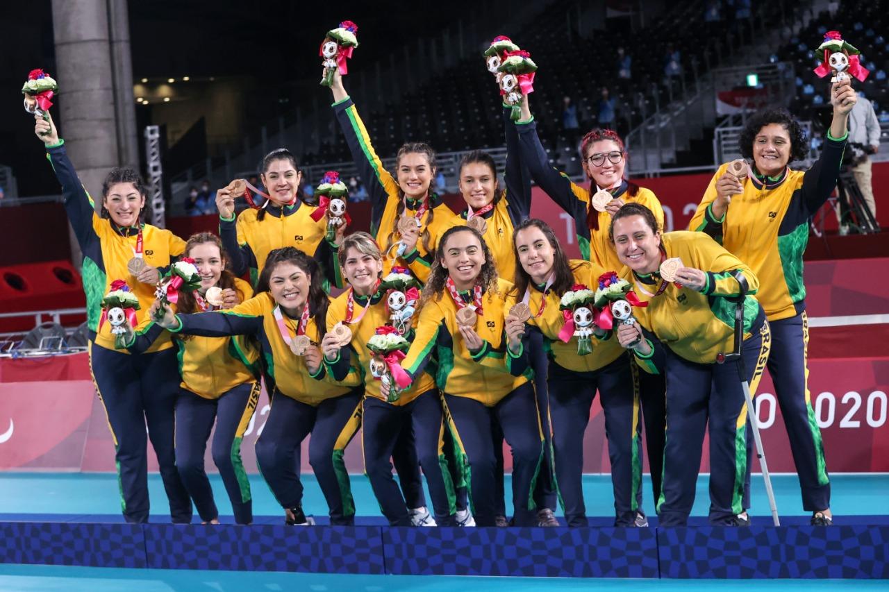 Time de vôlei sentado brasileiro em pé no pódio segurando mascote, medalhas e flores