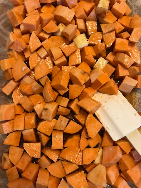 Baking dish with cubed and peeled sweet potatoes and spatula stirring the glaze before roasting.
