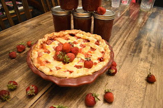 Wood grain table top with a lattice topped strawberry pie and a handful of fresh strawberries strewn about.