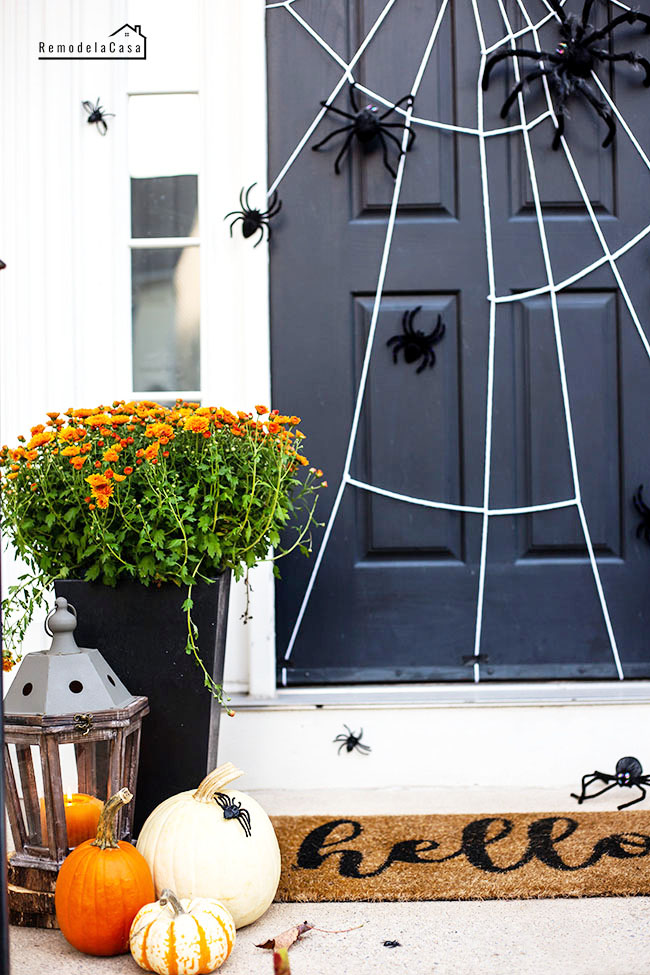 spider web and spiders on door Halloween porch with pumpkins and lanterns