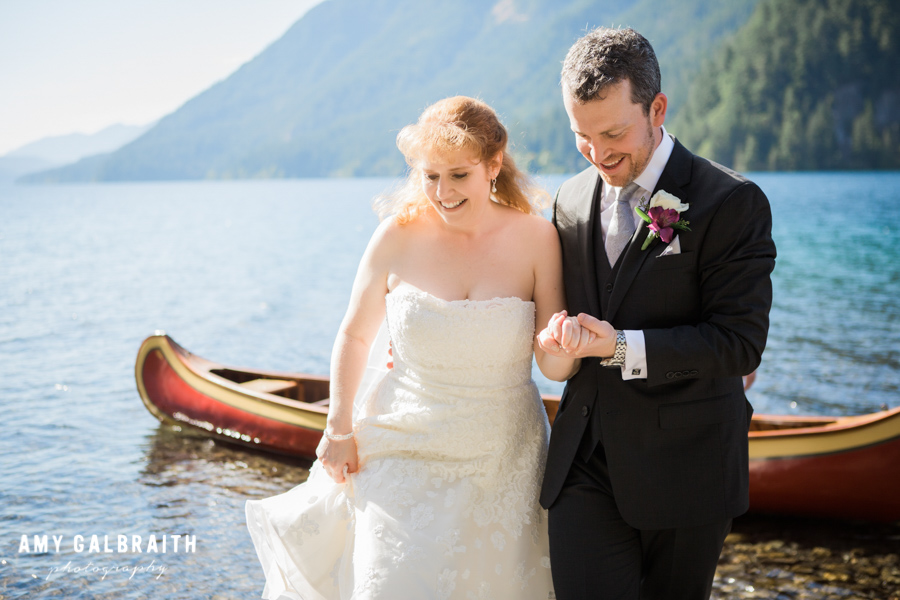 groom helping bride out of canoe