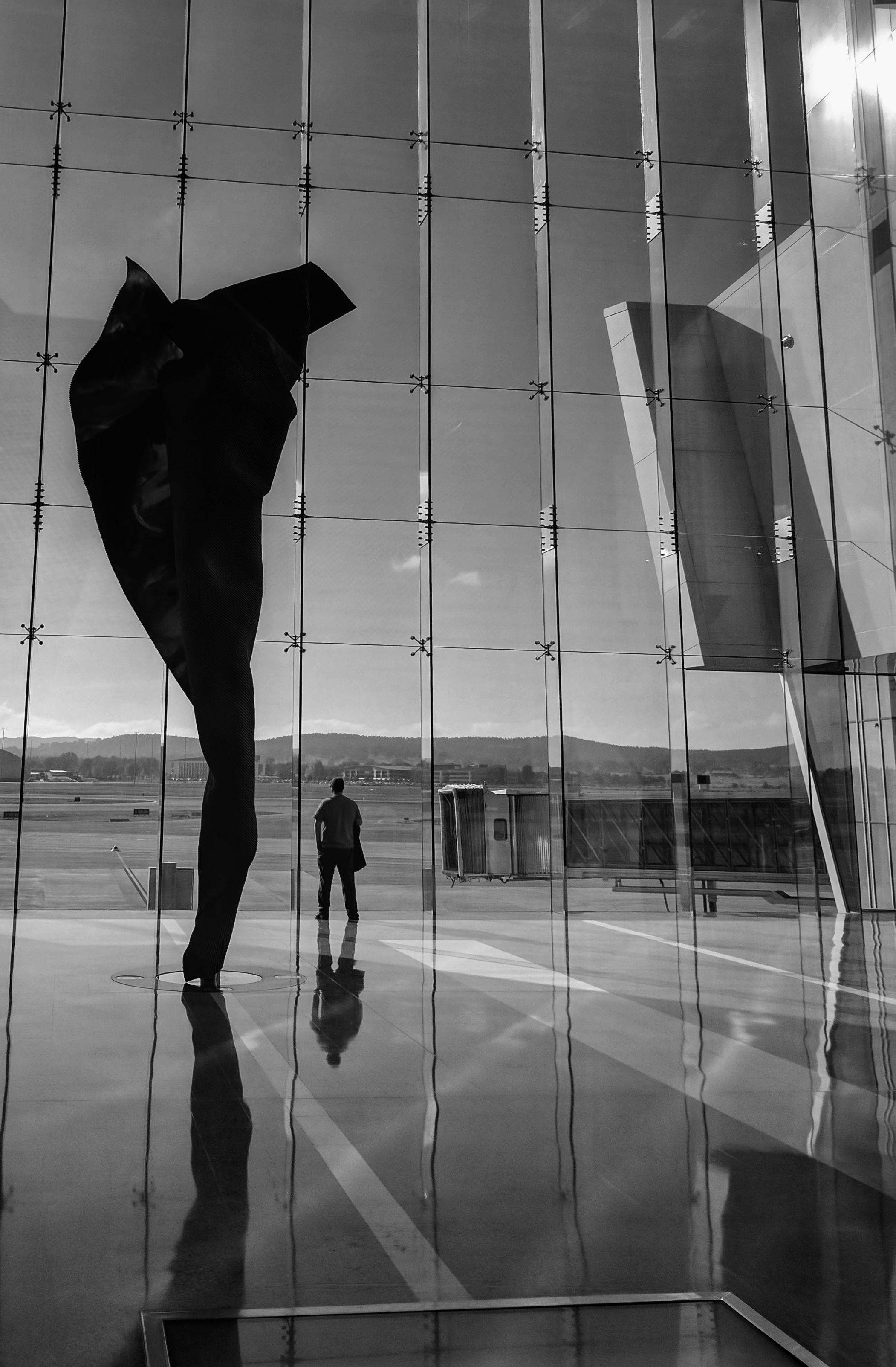 Black and white view of sculpture and person against window wall at Camberra sirport