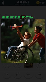 На поляне в коляске мальчик инвалидность, которого везет другой подросток