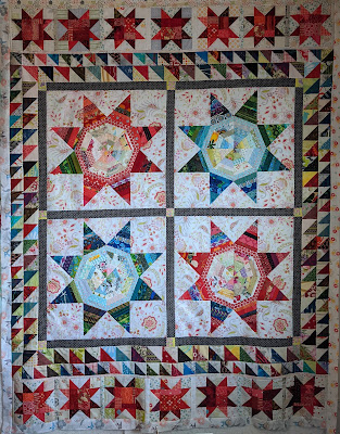 A narrow third border of cream print surrounds the Sawtooth Stars and HSTs to finish the LeMoyne Star string quilt top.