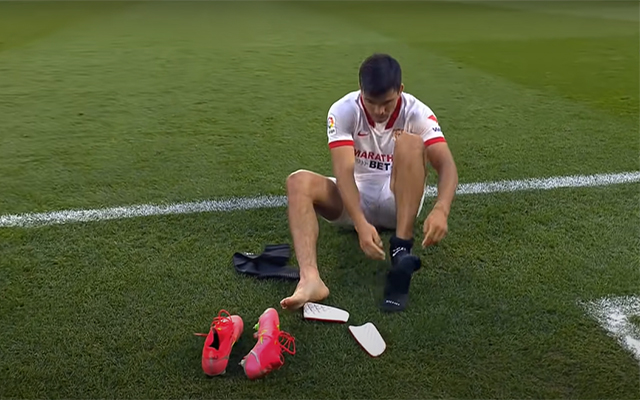 Sevilla player Marcos Acuña is seen wearing his socks to resume play against Granada after the referee blew too early for full-time