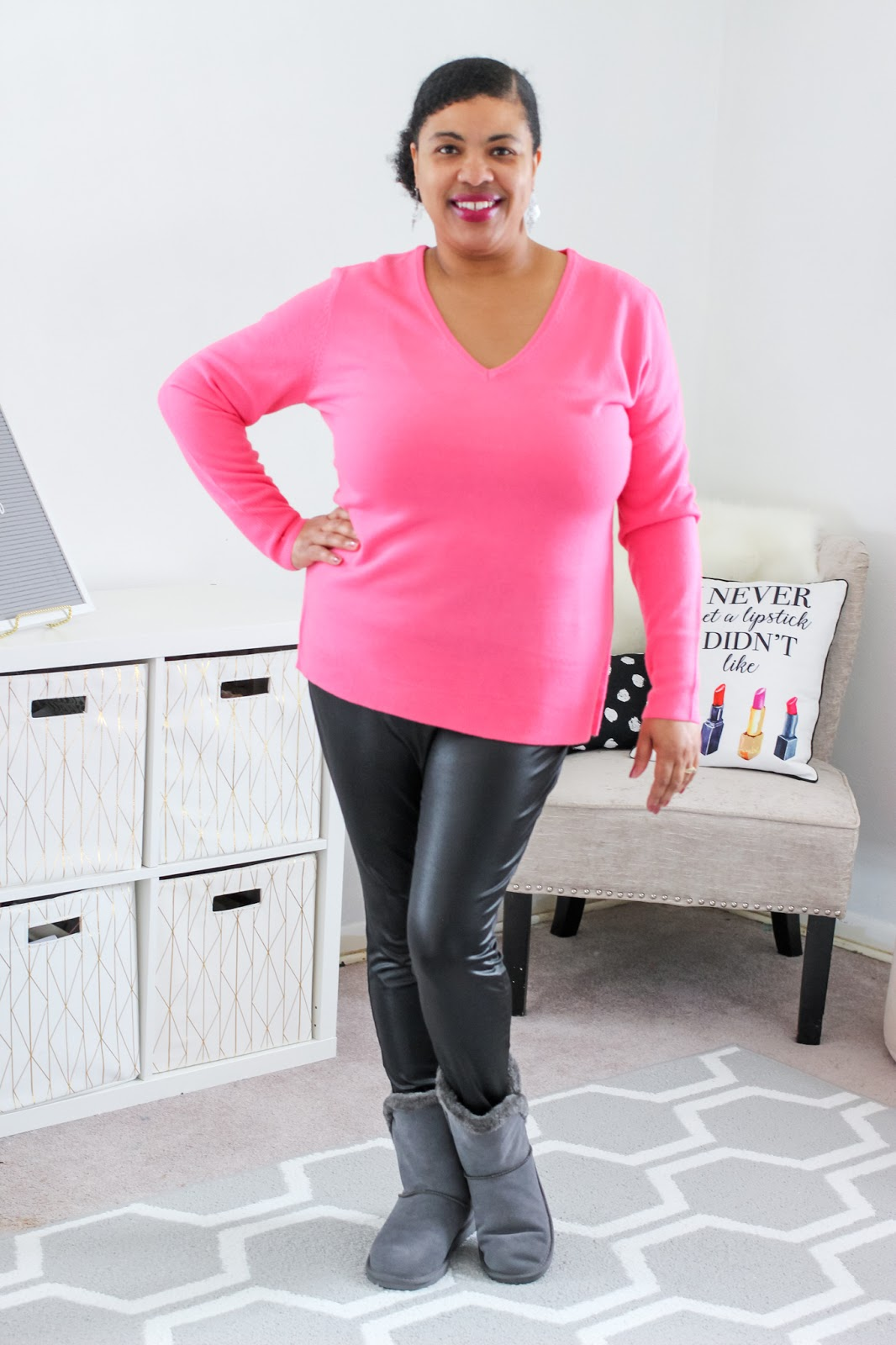 a woman wearing a pink sweater outfit
