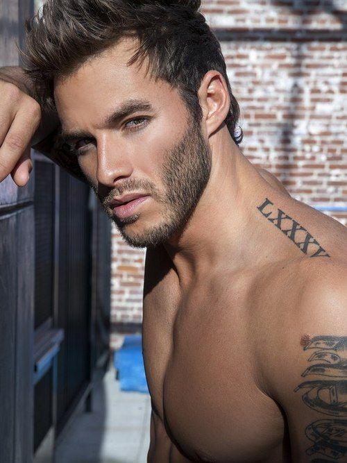 Chico modelo de mirada fuerte, apoyado en una pared, lleva tatuaje de números romanos en trapecio