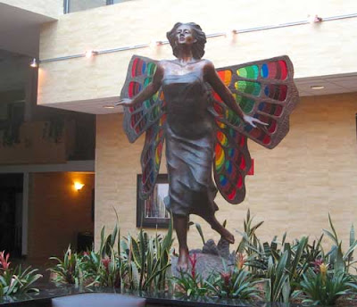 Bronze statue of a running girl with huge butterfly wings in rainbow stained glass