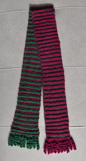 The finished scarf in full, folded at the top with the ends spread out to show the top side and the underside of red and green striped reversible fabric.The scarf is fringed with crocheted spiral curlicues.