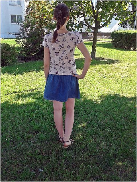 Pleciony warkocz, bluzka w kwiaty, jeansowa spódnica, sandały z ćwiekami