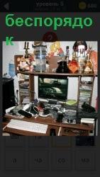 Стол на котором разбросаны вещи в беспорядке и сверху на полке полный бардак