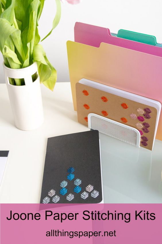 embroidered notebooks with leaf pattern on desk with colorful file folders