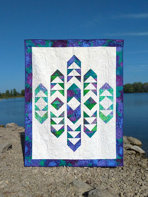 Quilt with purple and green on a white background, with a lake and blue sky in the photo background.