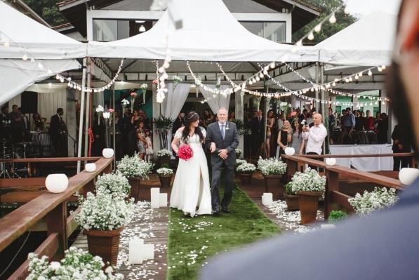 A imagem mostra uma noiva com buquê na mão indo até o altar ao encontro do noivo acompanhada de seu pai.