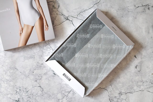 Birds eye view of the Wolford Jamaika String Body in the box on a marble background