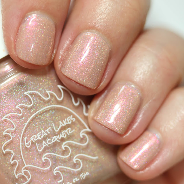 peachy holographic nail polish with red shimmer swatched on white person's nails