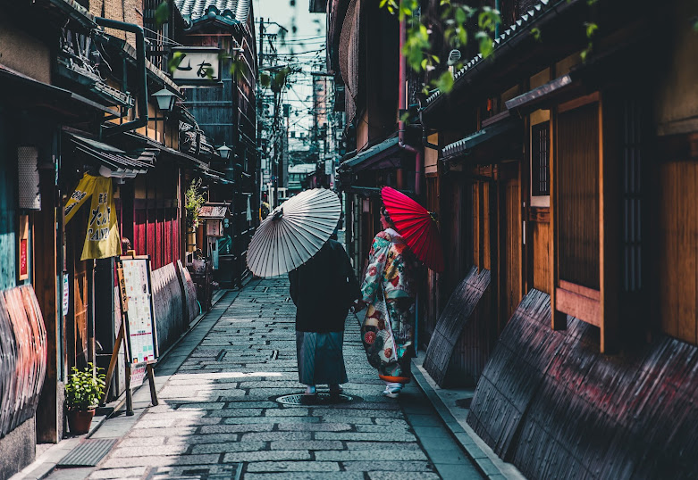 A colorful street with bricked ground and two women holding umbrellas walking together while they are talking to each other.