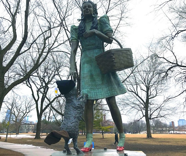 Toto hopping on Dorothy as she walks in her dazzling Ruby Slippers at Oz Park.