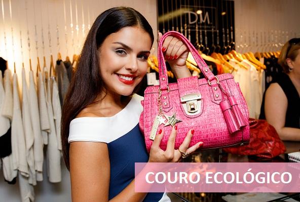 Modelo segurando bolsa Fellipe Krein rosa de couro ecológico.