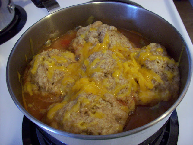 Cheese Dumplings simmering in pot of Tomato Stew.