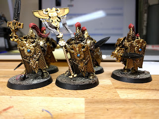 Custodes with red and gems painted, waiting on power effects