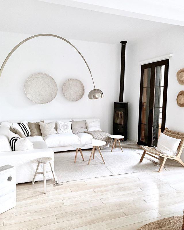 Salón blanco y natural con muebles y objetos de mimbre y de madera clara