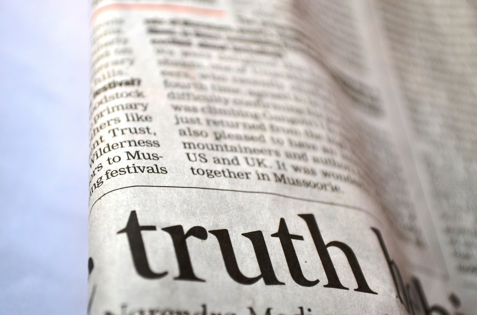 folded newspaper with the word truth in large letters to illustrate a blog post about war movies about true stories