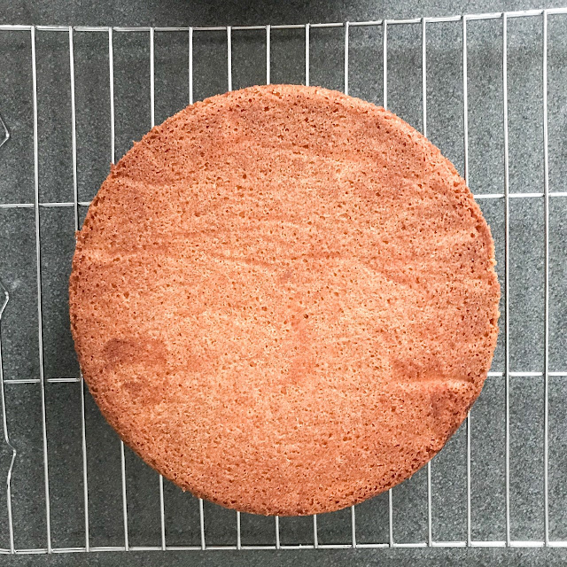 One of the baked cake layers on a wire tray