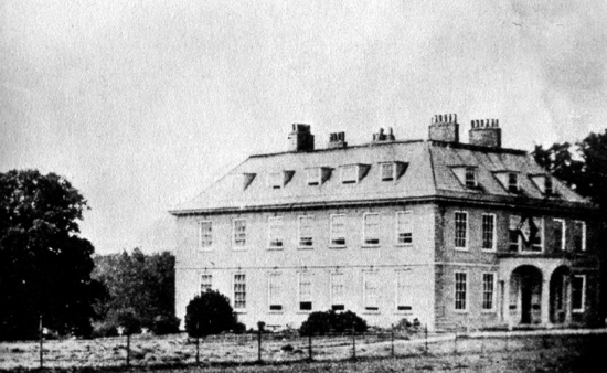 Photograph of Brookmans House in 1864. The hatchment above the front door is that of Mrs. E. C. Gaussen, who had died during that year.