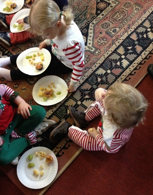 toddlers sat on floor with food on plates