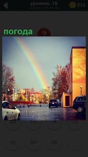 Вдали улицы в небе в результате изменения  погоды появилась радуга