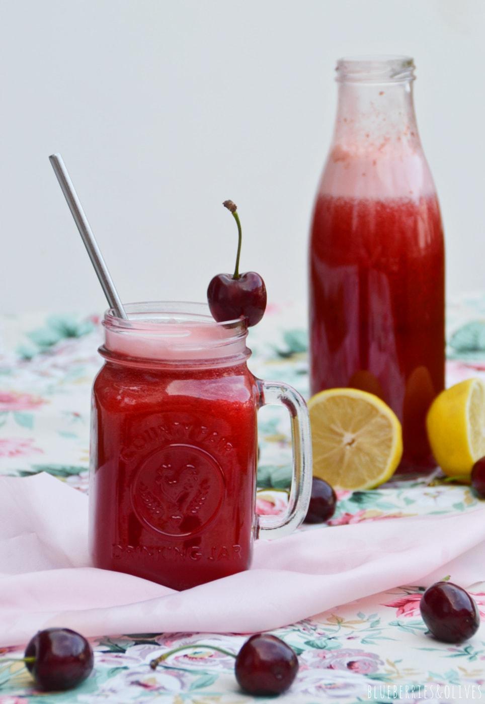 cherry lemonade in a glass jar, cristal bottle full, flowered table cloth, white background